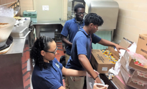 Bishop Grimes High School seniors Katie Collins, left, Marlyn Brown, center, and Lual Lual, rear, pack bags of food for students at Franklin Elementary School in Syracuse.(James T. Mulder)