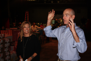 Tabitha and Jim Furyk address and thank the group of volunteers prior to the beginning of the packing process. Photo by Jon Blauvelt