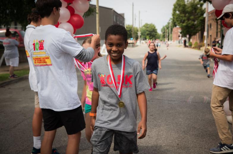 Boy crossing finish line at 0.5K in Louisville