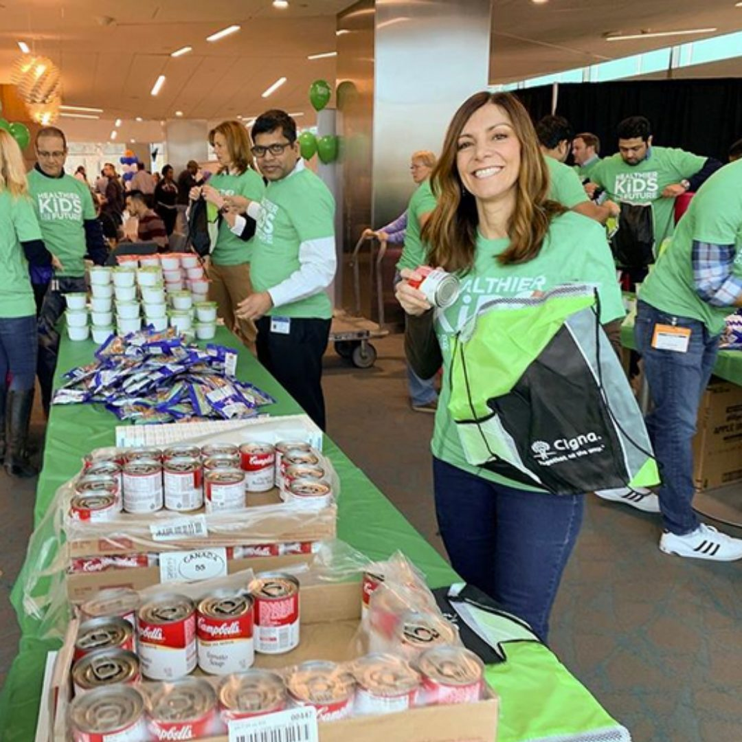 Cigna employees pack bags of food