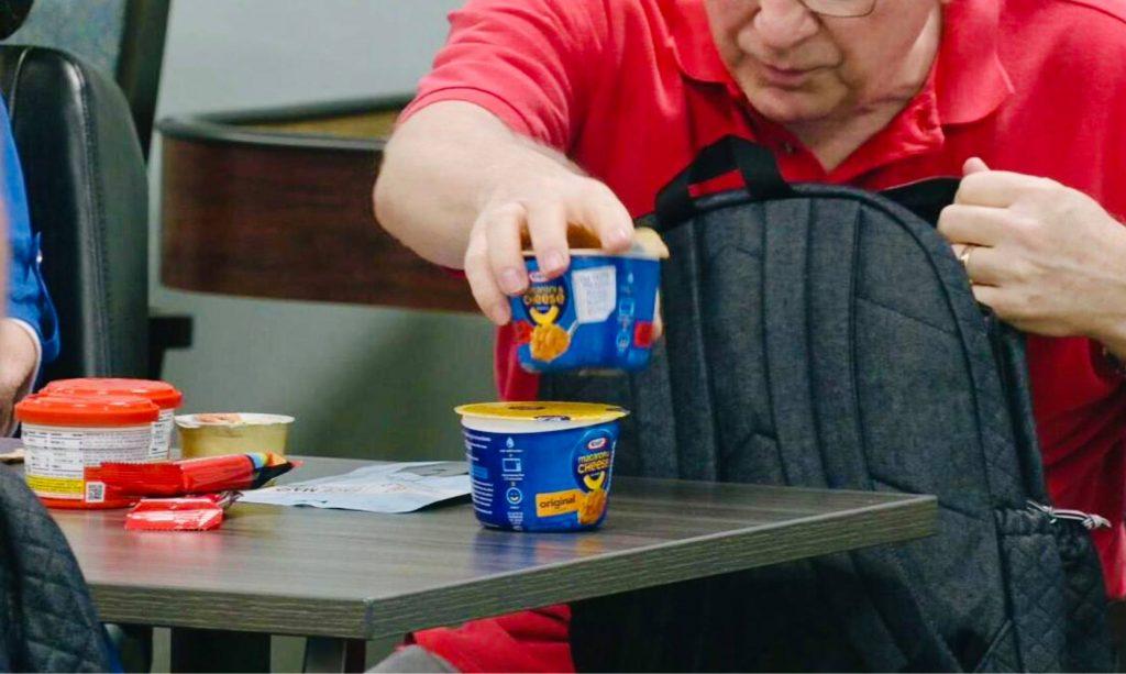 senior man putting food in backpack